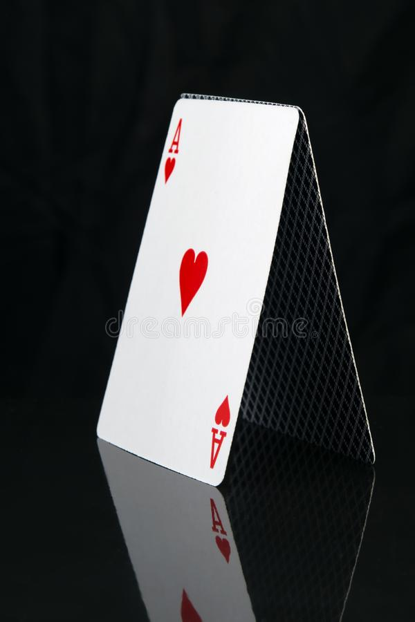 Karte für ein Pokerspiel, steht eine Pyramide, auf einem schwarzen Hintergrund mit Reflexion, Nahaufnahme lizenzfreie stockfotografie