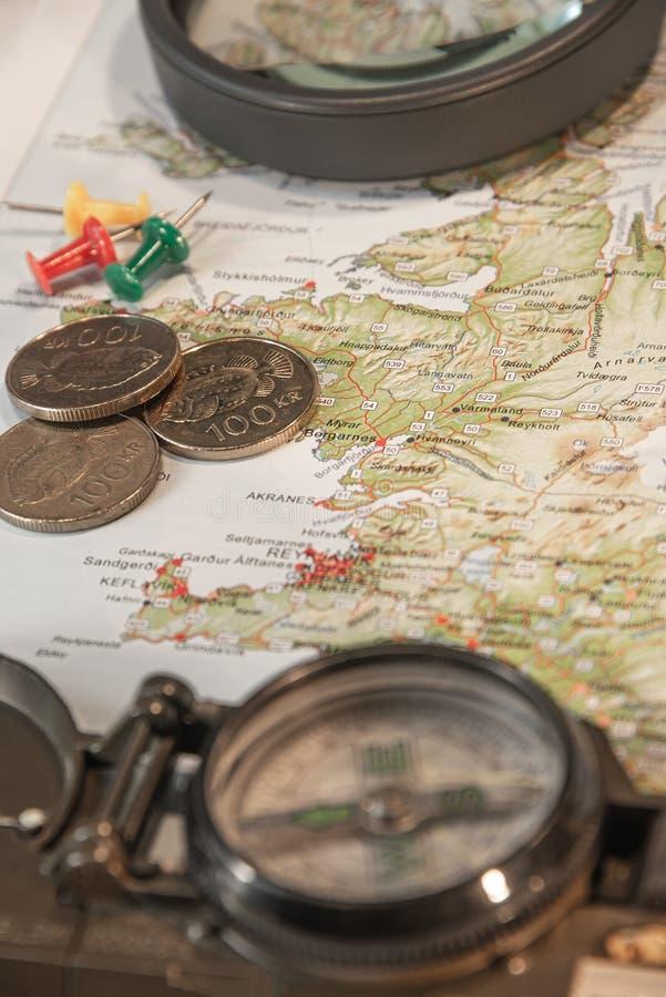 Karte von Island, von Stoßstiften, von Kompass, von isländischem Geld und von Linsenvergrößerungsglas als entscheidenden Einzelte stockbild