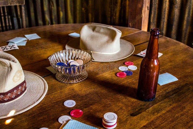 Karten, Pokerchips, Bierflasche und Cowboy Hats auf einem hölzernen Tabl lizenzfreies stockbild