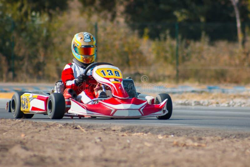 Karting - motorista no capacete no circuito do kart imagem de stock