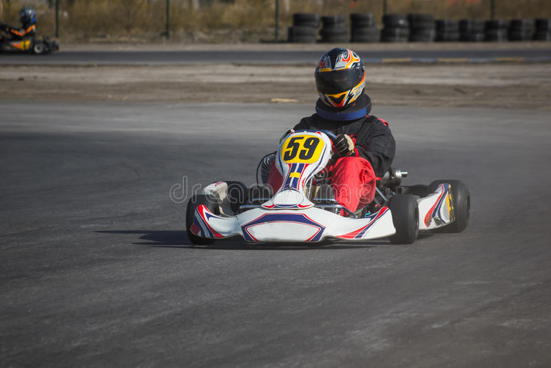 Karting - motorista no capacete no circuito do kart fotografia de stock