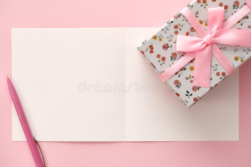 Kartka z pozdrowieniami, prezenta pudełko i pióro w różowych kolorach, zdjęcie royalty free