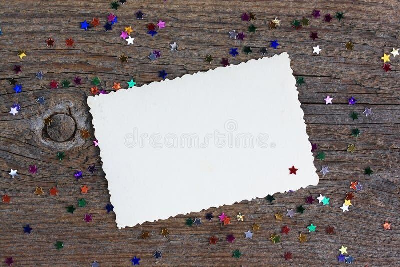 Kartka z pozdrowieniami: pusta papier forma z gwiazda confetti na drewnianym tle obrazy royalty free