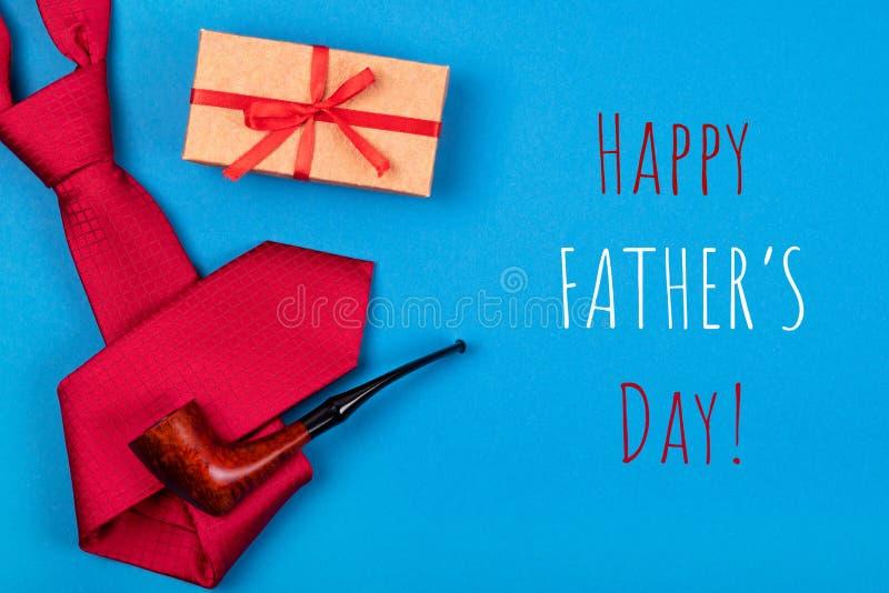 Kartka z pozdrowieniami z składem czerwony szyja krawat, prezenta pudełko i dymić tabaczną drymbę z wpisowym Szczęśliwym ojca dni fotografia royalty free