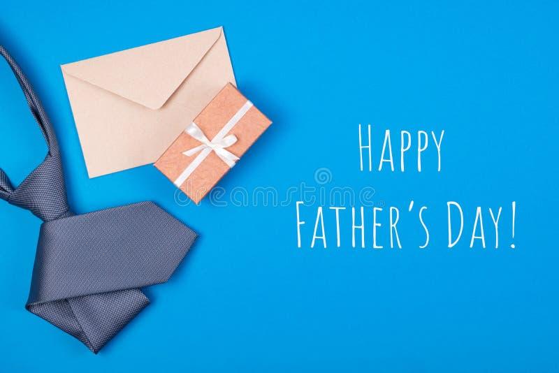 Kartka z pozdrowieniami z składem popielaty szyja krawat, prezenta pudełko, rzemiosło koperta na błękitnym tle z wpisowym Szczęśl obraz stock