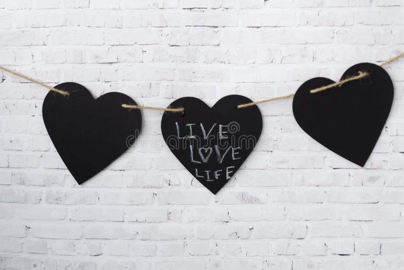 Kartka z pozdrowieniami valentine Trzy serca wieszają na arkanie na cegły światła ścianie, obrazy stock