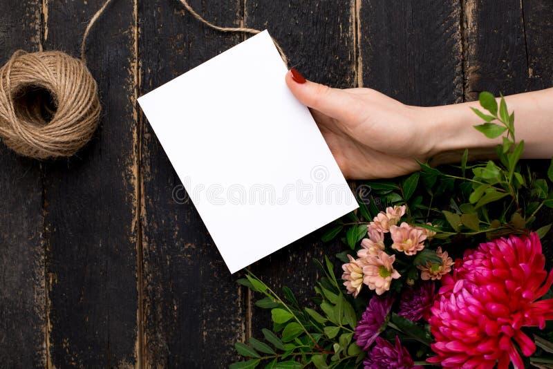 Kartka z pozdrowieniami w ręce z bukietem kwiaty na ciemnego rocznika drewnianym tle zdjęcie royalty free