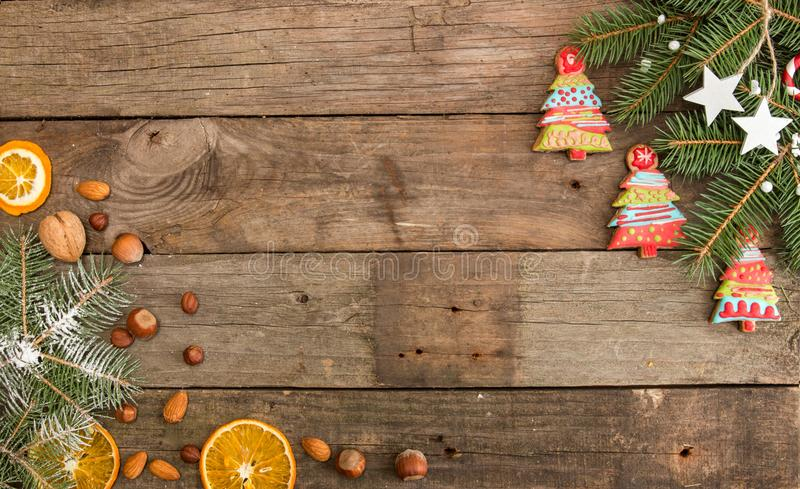 Kartka z pozdrowieniami z wystrojów piernikowymi ciastkami, jedlinowa gałąź dalej fotografia stock