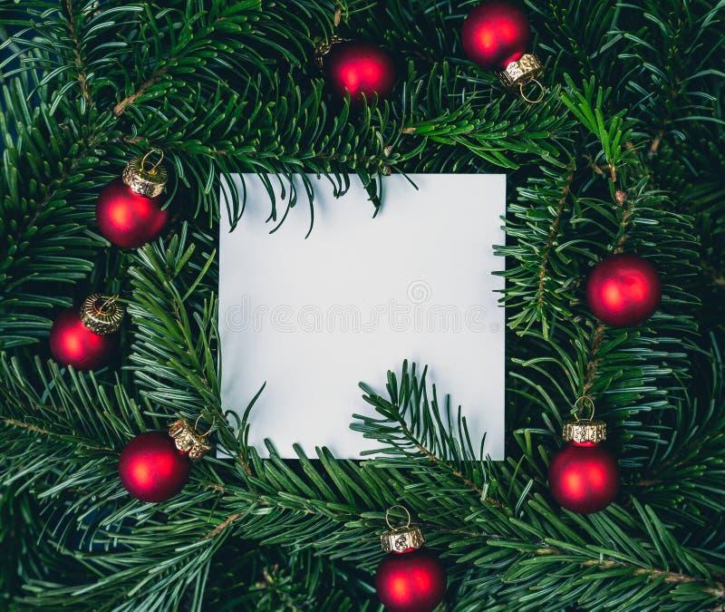 Kartki bożonarodzeniowej notatka na zielonych świerkowych gałąź z czerwonymi piłkami zdjęcie royalty free