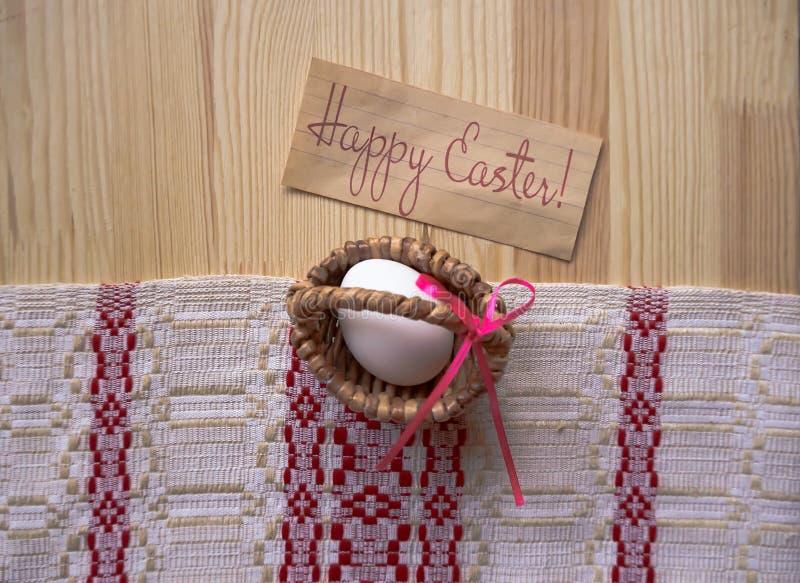 Kartki z pozdrowieniami Szczęśliwa wielkanoc! Biały Wielkanocny jajko w mini koszu na drewnianym tle z tablecloth obraz stock