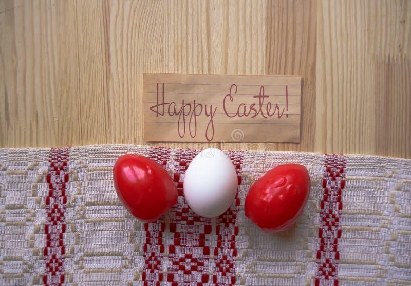 Kartki z pozdrowieniami Szczęśliwa wielkanoc! Trzy Wielkanocnego jajka czerwony i biały kolor na drewnianym tle z tablecloth zdjęcia stock