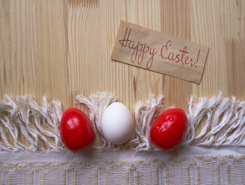 Kartki z pozdrowieniami Szczęśliwa wielkanoc! Trzy Wielkanocnego jajka czerwony i biały kolor na drewnianym tle z tablecloth Wieś obrazy royalty free