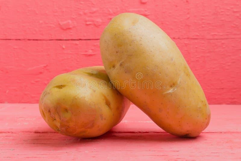 Kartoffel auf rosa Holz stockbilder