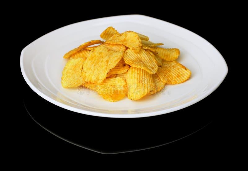 Kartoffelchips auf einer Platte auf einem schwarzen Hintergrund lizenzfreies stockfoto