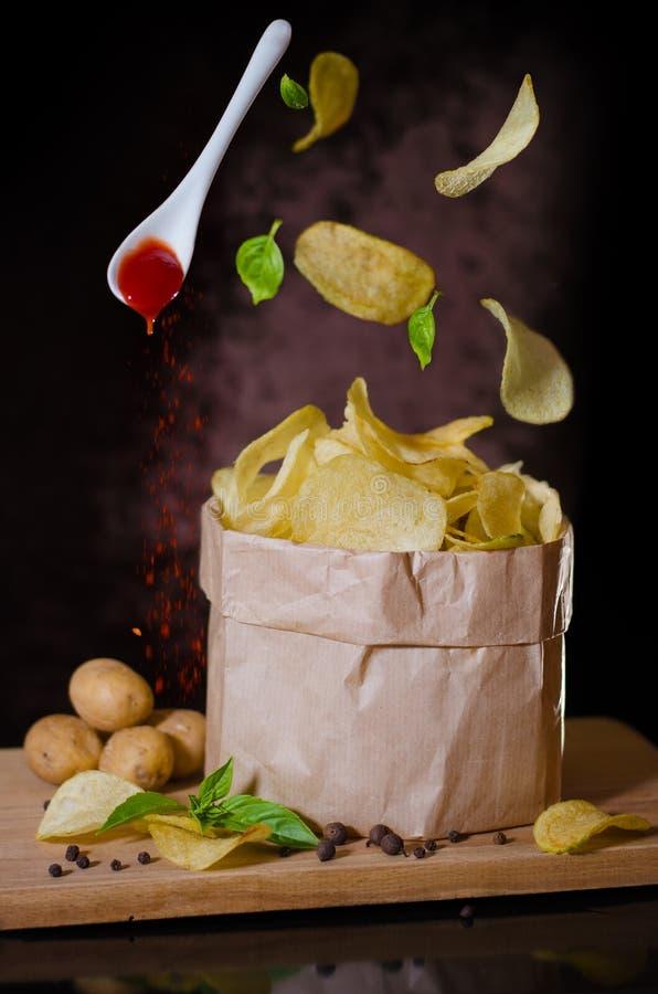 Kartoffelchips, die über eine Schüssel fliegen lizenzfreies stockfoto