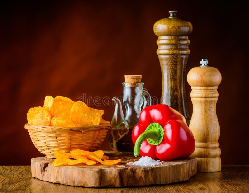 Kartoffelchips, roter Pfeffer und Bestandteile stockfotos