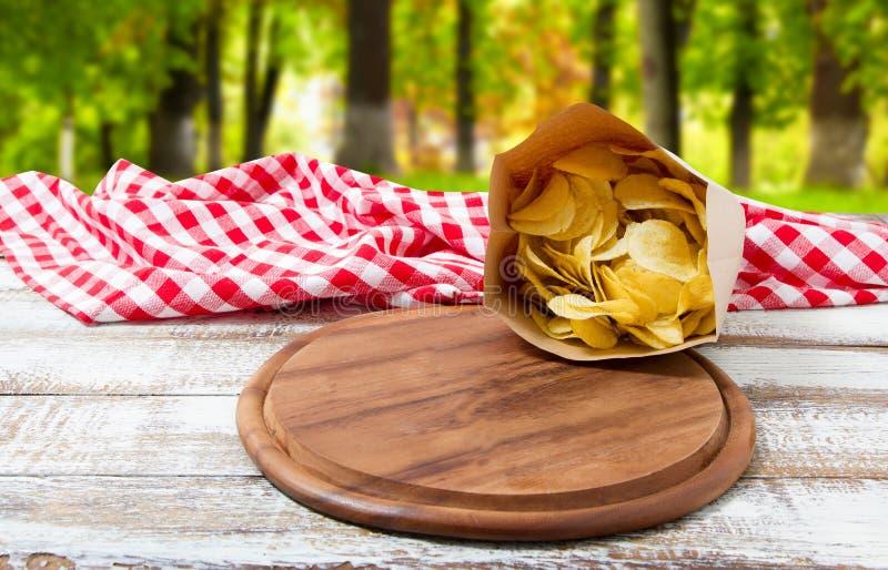 Kartoffelchips verpacken, Pizzaschreibtisch und Tischdecke auf unscharfem Parkhintergrund lizenzfreie stockfotografie