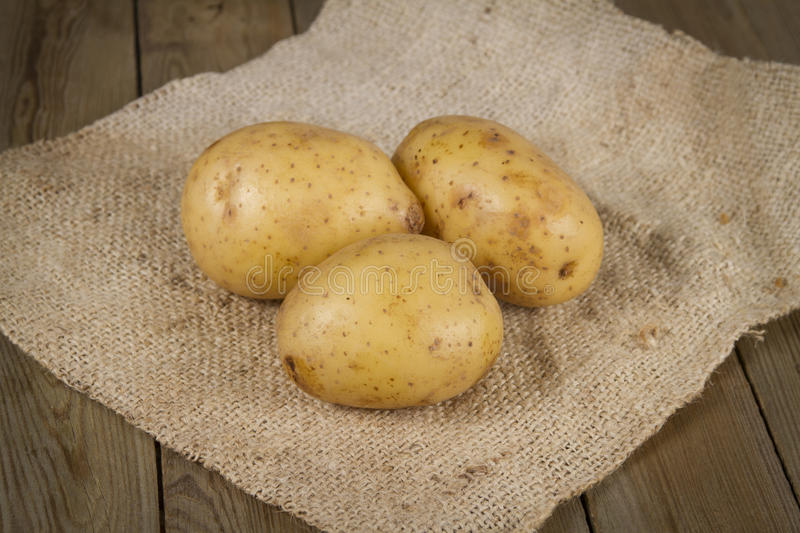 Potatoes. Three raw potatoes lying on a linen textile royalty free stock image