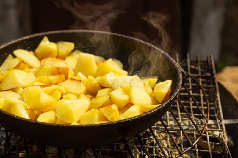 Kartoffeln brieten in einer Bratpfanne auf einem Grill lizenzfreies stockbild