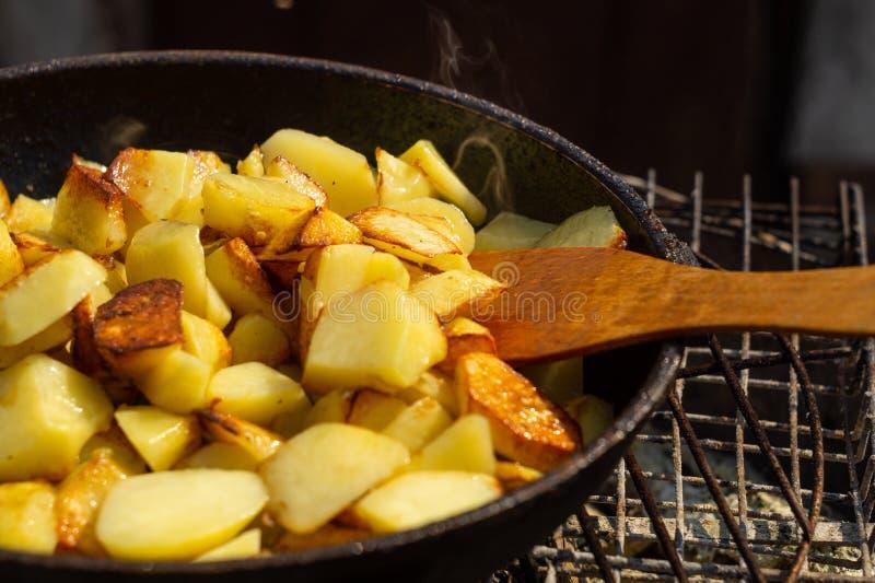 Kartoffeln brieten in einer Bratpfanne auf einem Grill lizenzfreie stockfotos