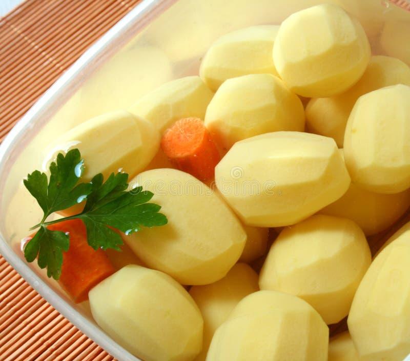 Kartoffeln in der Schüssel mit Wasser lizenzfreie stockbilder