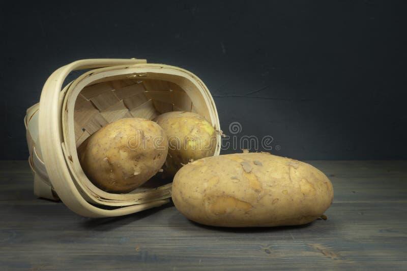 Kartoffeln, die aus gespitztem Weidenkorb heraus verschüttet werden stockbild