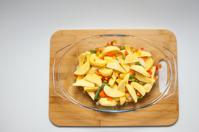 Kartoffeln mit dem Gemüse gebacken im Ofen in einem Glasbehälter mit einem Deckel Schneidebrett und weißer Hintergrund lizenzfreie stockfotografie