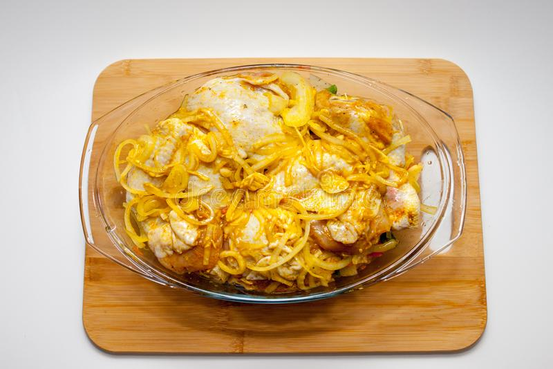 Kartoffeln mit dem Gem?se gebacken im Ofen in einem Glasbeh?lter mit einem Deckel Schneidebrett und wei?er Hintergrund lizenzfreie stockbilder
