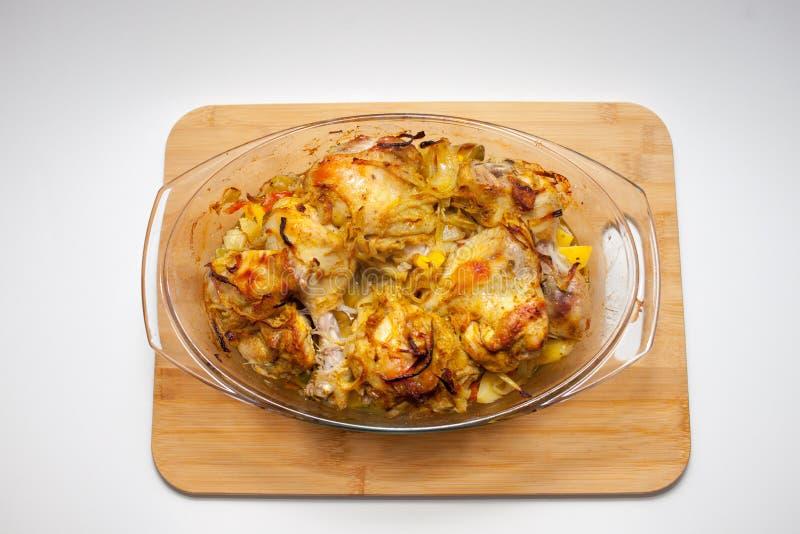 Kartoffeln mit dem Gem?se gebacken im Ofen in einem Glasbeh?lter mit einem Deckel Schneidebrett und wei?er Hintergrund lizenzfreies stockbild