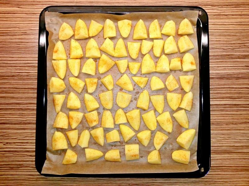Kartoffeln roh auf Backpapier im Backblech lizenzfreie stockfotografie