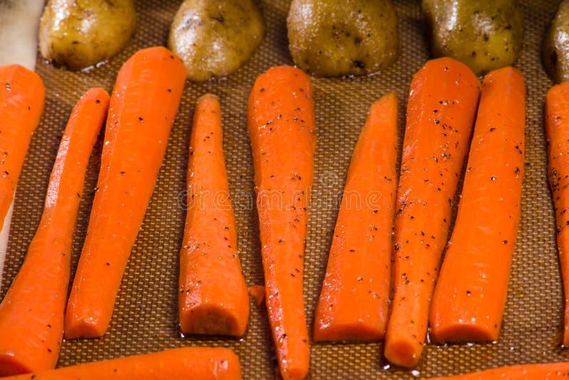 Kartoffeln und Karotten auf einem Backblech stockfotos