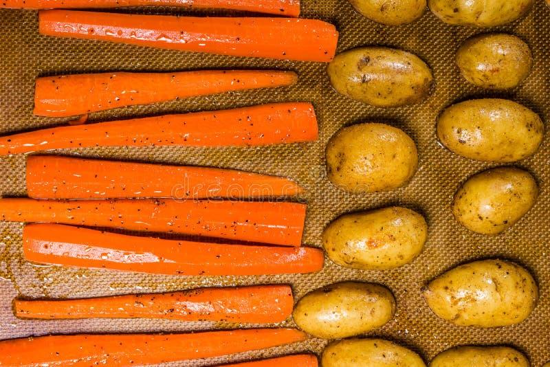 Kartoffeln und Karotten auf einem Backblech lizenzfreie stockfotos