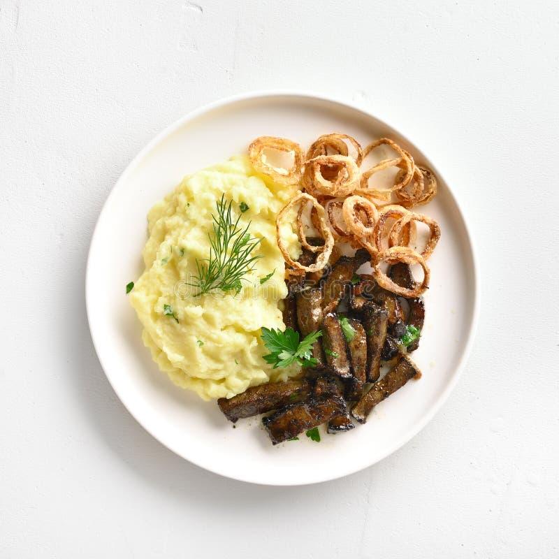 Kartoffelpürees mit der Leber des gebratenen Rindfleisches und den gebratenen Zwiebelringen stockbilder