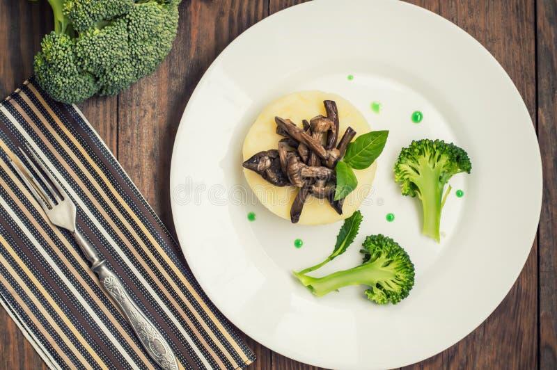Kartoffelpürees mit Pilzen und gekochter Brokkolisoße Hölzerner Hintergrund Beschneidungspfad eingeschlossen Nahaufnahme lizenzfreie stockfotografie