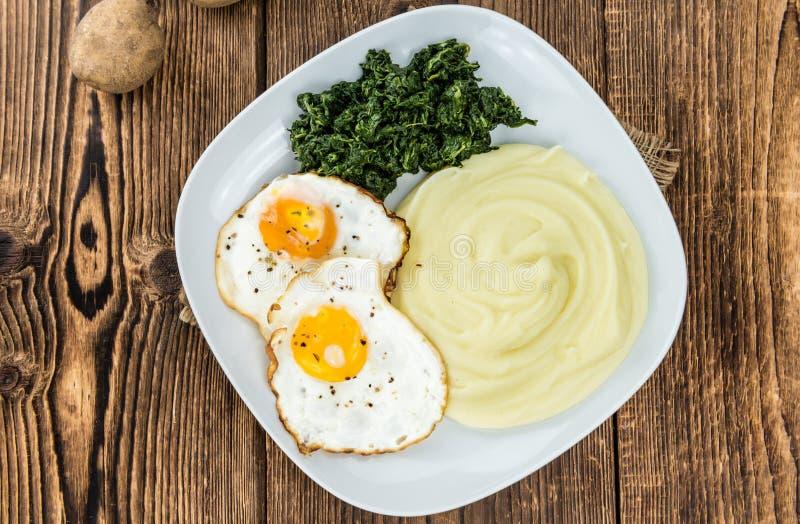 Kartoffelpürees mit Spinat und gebratenem egga selektivem Fokus lizenzfreie stockfotos