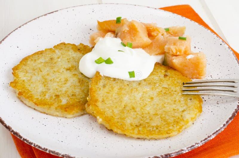 Kartoffelpfannkuchen mit weißer Soße und geräuchertem Lachs lizenzfreie stockfotografie