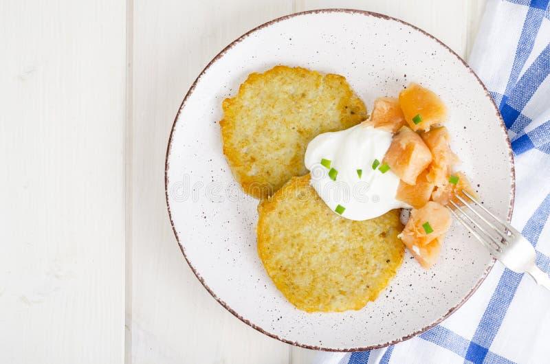 Kartoffelpfannkuchen mit weißer Soße und geräuchertem Lachs stockbild