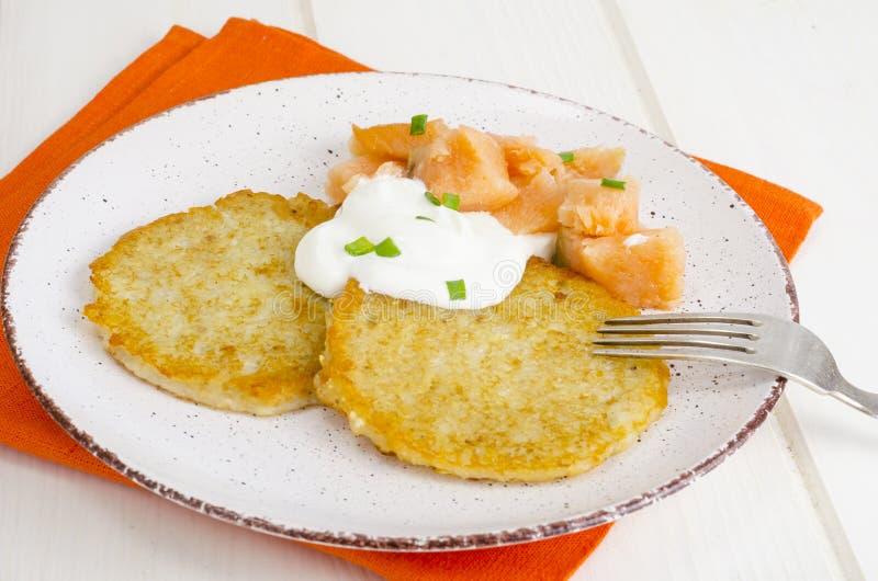Kartoffelpfannkuchen mit weißer Soße und geräuchertem Lachs stockfoto