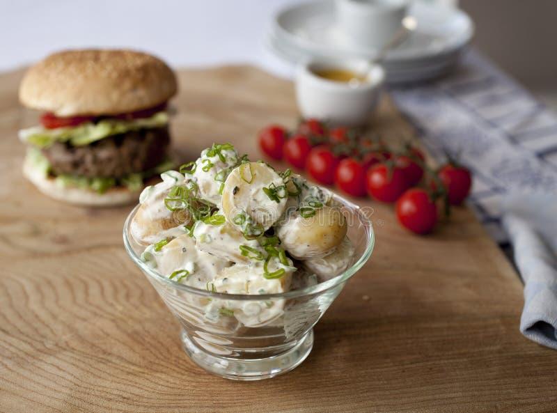 Kartoffelsalat mit Burger im Hintergrund. lizenzfreies stockbild