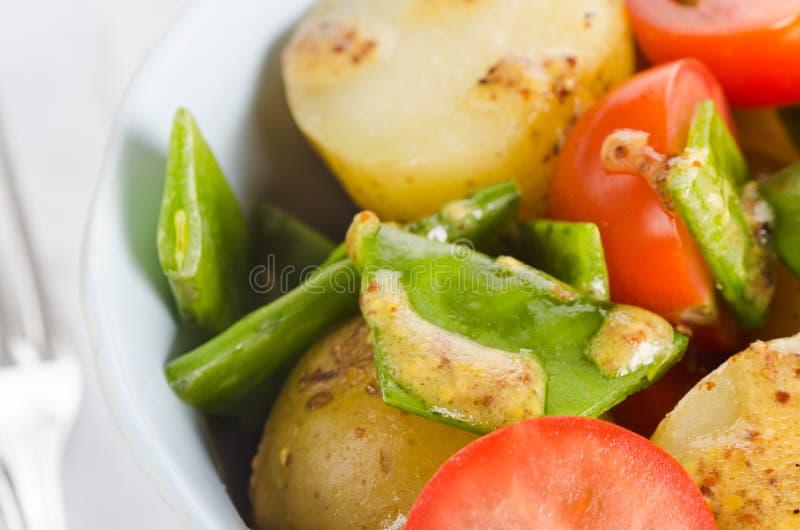 Kartoffelsalat mit Kirschtomaten und Schneeerbsen mit Ölsenf lizenzfreie stockbilder