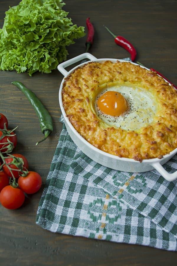 Kartoflana potrawka z Bolognese Piec kartoflana potrawka z jajkiem i kraciastym serem w ceramicznym owalnym wypiekowym prze?ciera zdjęcia stock