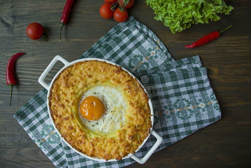Kartoflana potrawka z Bolognese Piec kartoflana potrawka z jajkiem i kraciastym serem w ceramicznym owalnym wypiekowym prze?ciera zdjęcie royalty free