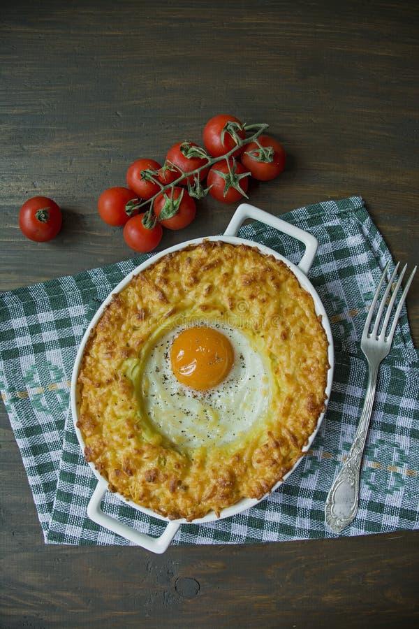 Kartoflana potrawka z Bolognese Piec kartoflana potrawka z jajkiem i kraciastym serem w ceramicznym owalnym wypiekowym prze?ciera fotografia royalty free