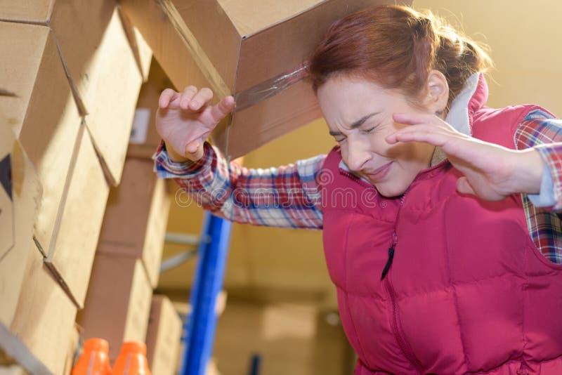 Karton, der auf den Kopf der Frau an der Fabrik fällt stockfoto