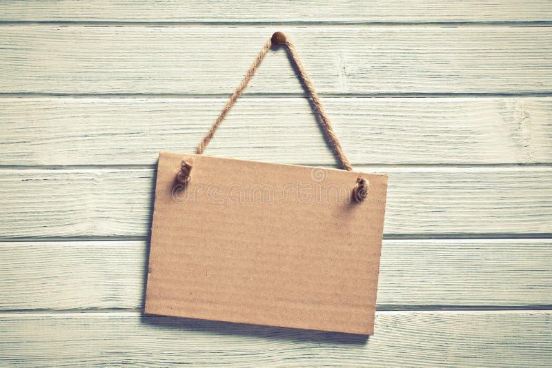 Karton het hangen op houten muur royalty-vrije stock afbeeldingen