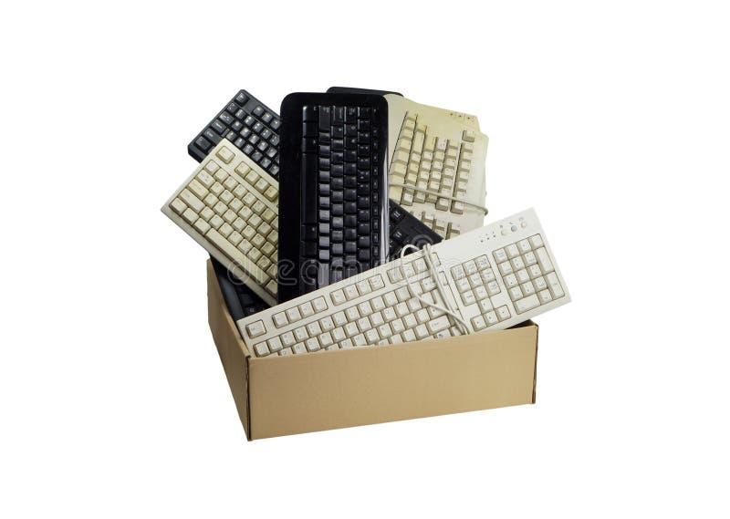 Kartondoos met gebruikte computertoetsenborden dat wordt gevuld Elektronisch Afval stock afbeeldingen
