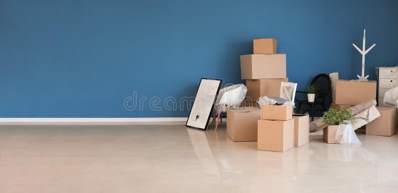 Kartondozen en binnenlandse die punten op zich het bewegen in nieuw huis dichtbij kleurenmuur worden voorbereid stock foto
