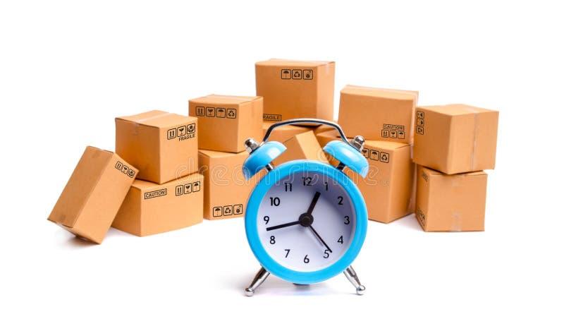 Kartonger och klocka på vit bakgrund Tid av leveransen begrepp av köpande och säljavaror och tjänst, arkivfoto