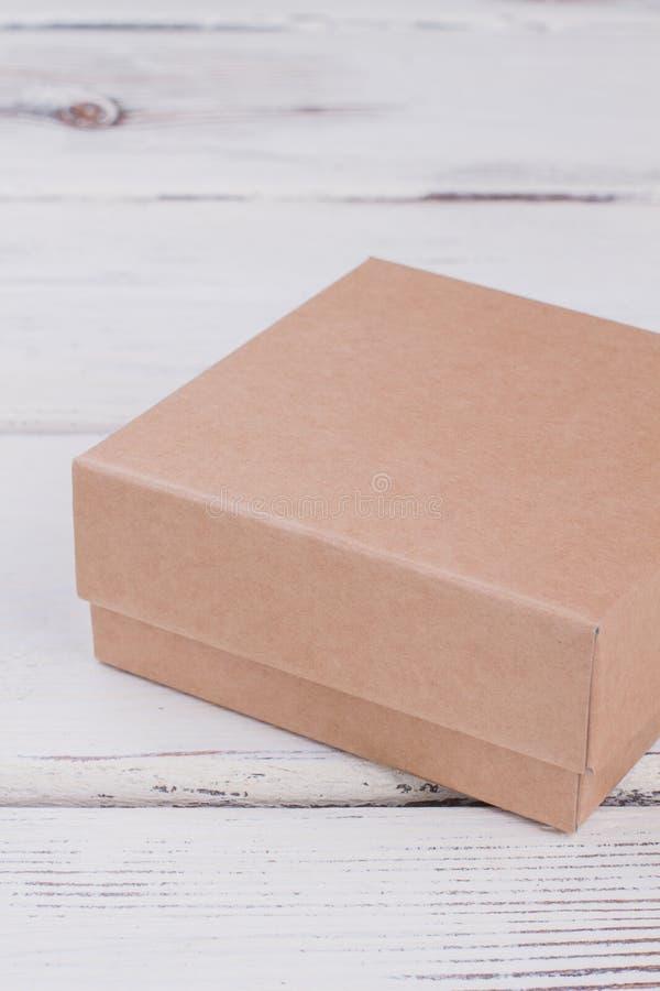 Kartongeschenkbox auf hölzernem Hintergrund stockbild