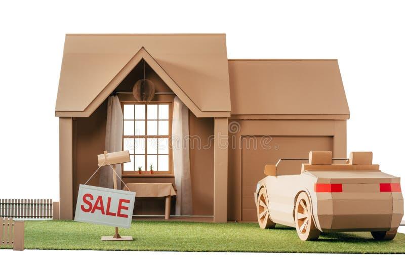 kartonhuis en auto met tekenverkoop op wit wordt geïsoleerd dat royalty-vrije stock afbeeldingen